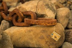The Chain Bible. Small gold Holy Bible connected to a big old rusted chain links stock photography