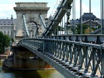 The Chain bridge in Budapest in diminishing perspective. The Chain bridge in Budapest, Hungary in diminishing perspective over the green water of the Danube royalty free stock photography