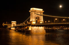 The Chain Bridge in Budapest with full moon. The Chain Bridge with the Gresham Palace and Danube river in Budapest at full moon - Hungary at night Royalty Free Stock Photography