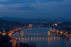 Chain Bridge in floodlight in Budapest, Hungary. The Chain Bridge over the Danube river with the hills of Buda in the background at dusk, in floodlight in Royalty Free Stock Photography