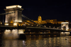 The Chain Bridge in front of the Gresham Palace in Budapest. A night view of the Szechenyi Chain Bridge, a suspension bridge over the River Danube in Budapest Stock Photo