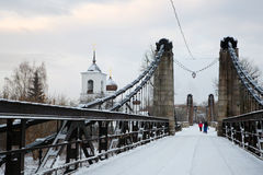 Chain Bridge of Island and the church of St. Nicholas. January 3, 2017 g, a unique Chain Bridge and St. Nicholas Church in the city Island of the Pskov region stock photography