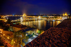 Chain Bridge leading to the St Stephen`s Basilica at night stock photography