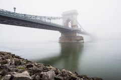 Chain Bridge over the Danube and a boat, Budapest, Hungary, in  fog, evening lights Royalty Free Stock Photos