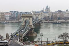 Chain bridge over Danube river with cars, tram and motor ship in Budapest, Hungary. Beautiful view at Pest side. Royalty Free Stock Images