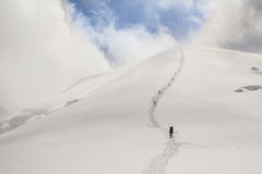 A chain of climbers climbing to the top of the mountain Royalty Free Stock Photo