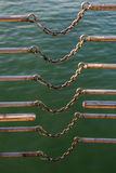 chain connects two metal bars over body of water Royalty Free Stock Image