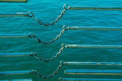 chain connects two metal bars over body of water Royalty Free Stock Photos