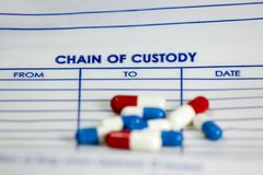 Chain of custody. Here is an evidence bag with pills on top of it Stock Photography