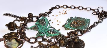 Chain with decorative green butterflies, leaves, flowers, frame, hearts and beads royalty free stock image