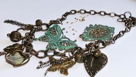 Chain with decorative leaves, beads, green butterflies and frame with rhinestones stock photos