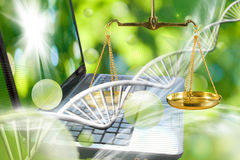 Chain of dna, laptop and scales on green background Royalty Free Stock Photos