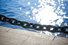 Chain on the dock. In the background sparkling in the sun water Stock Images