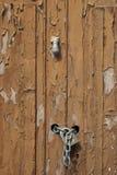 Ocher door. Chain door knocker on wooden door painted with ocher Stock Photography