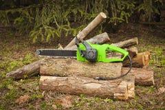 The chain electric saw . The chain electric saw lies on logs Stock Photos