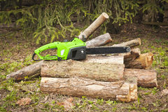 The chain electric saw . The chain electric saw lies on logs Royalty Free Stock Images