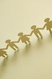Chain of figures. Vertical image of paper figures Royalty Free Stock Images