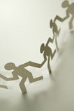 Chain of figures. Vertical image of paper figures Royalty Free Stock Image