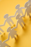 Chain of figures. Vertical image of paper figures Royalty Free Stock Photos