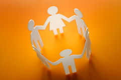 Chain of figures. Orange background Royalty Free Stock Photo