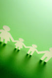 Chain of figures. Green background Stock Photography