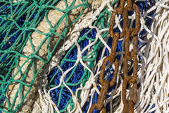 Chain on a fishing net. Close-up of fishing nets stacked in the harbor, paying particular attention to the colors, textures, materials, details, knots, etc royalty free stock images