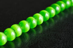 Chain of green beads on a black background Stock Photo