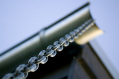 Chain hanging from the rain gutter on a house Stock Photos