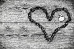 Chain heart shape with lock on wooden backround. Stock Photo