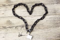 Chain heart shape with open lock on wooden backround.  Royalty Free Stock Photos
