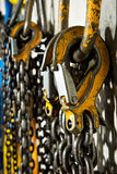 Chain Hoists. Several large industrial weathered yellow hooks attached to chain and a pulley royalty free stock photography