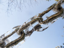 Chain in ice. Close-up of frozen chain links against bright blue sky Royalty Free Stock Images