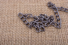 Chain on a linen canvas as background texture. Chain on a linen canvas as a background texture Royalty Free Stock Photos