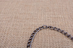 Chain on a linen canvas as background texture. Chain on a linen canvas as a background texture Royalty Free Stock Image