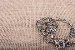 Chain on a linen canvas as background texture. Chain on a linen canvas as a background texture Royalty Free Stock Photo