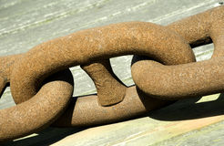Chain Link. A very large rusted metal chain link at shipyard and wooden background Royalty Free Stock Photos