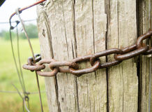Chain link around farm post. Detail of aged chain links around farm post in rural setting Royalty Free Stock Images