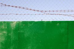Chain-link and barbed wire on top of green fence royalty free stock photography