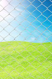 Chain link fence. See fresh grass and blue sky Royalty Free Stock Image