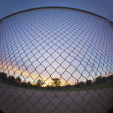 Chain Link Fence. Outside of a baseball field at sunrise. Shot with fisheye lens stock image