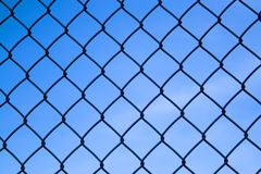 Chain Link Fence. Closeup detail of a chain link fence over a blue sky Royalty Free Stock Photos