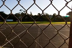 Chain Link Fence. A closeup of a chain link fense with a basketball court behind Stock Image
