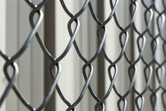 Chain link fence against a bokeh background of a metal building Royalty Free Stock Image