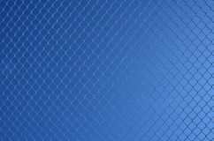 Chain link fence against sky. Chain link fence on a blue gradient sky background stock photo