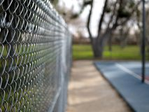 Chain link fence around basketball courts in park. Chain link fences around basketball courts in park Royalty Free Stock Photography