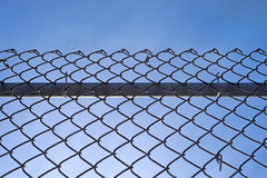 Chain link fence with bar against blue sky. A chain link fence with a sturdy bar behind the mesh and fastenings against a blue sky with wispy clouds Royalty Free Stock Photos