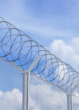 Chain link fence with barbed wire under blue sky. Chain link fence with barbed wire Royalty Free Stock Photography