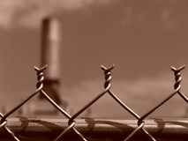 Chain Link Fence Barbs. Top of chain link fence with factory in background, west springfield, massachusetts Royalty Free Stock Photography