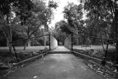 CHAIN LINK FENCE BRIDGE OVER CREEK. A narrow bridge over a creek has a chain link fence royalty free stock images