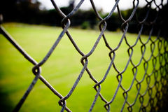 Chain Link Fence Closeup. A close up picture of a chain link fence with high contrast and green background stock photo